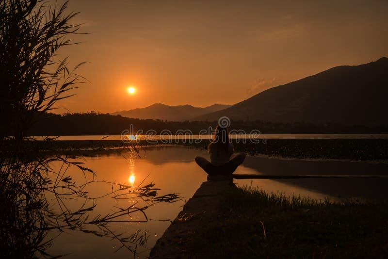Silhouette de fille se tenant au-dessus de l'amountain de lac en position de yoga de loto image stock