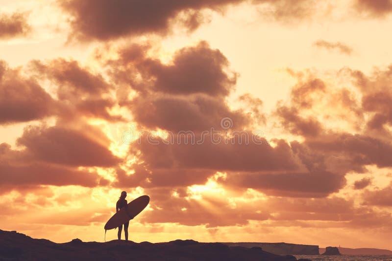 Silhouette de fille de surfer sur le coucher du soleil image stock