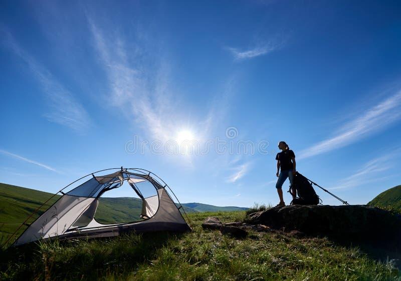 Silhouette de grimpeuse de femme près du camping contre le ciel bleu pendant le matin photo stock