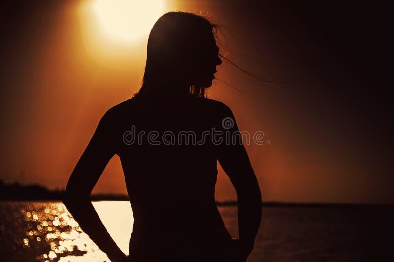 Silhouette de jeune belle fille au coucher du soleil images stock