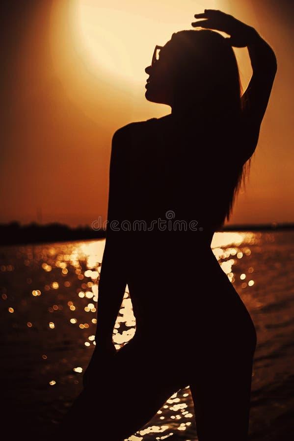 Silhouette de jeune belle fille au coucher du soleil photos stock