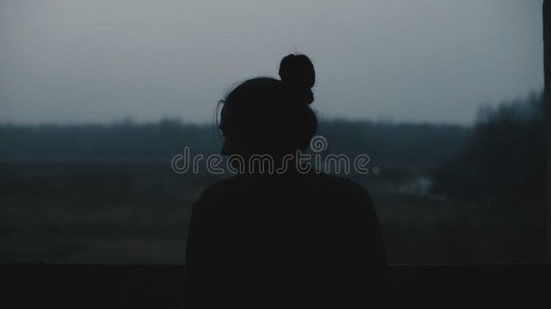 Silhouette de jeune belle fille dans le village Modèle sur le fond d'une fille de femme de forêt devant la fenêtre image libre de droits