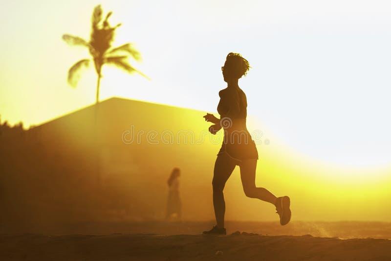 Silhouette de jeune femme attirante et convenable de coureur avec le corps sportif fonctionnant sur la belle formation de lumière photographie stock libre de droits