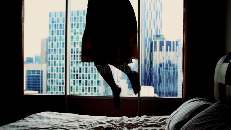 Silhouette de jeune femme heureuse dans la robe sautant sur le lit d'hôtel images stock