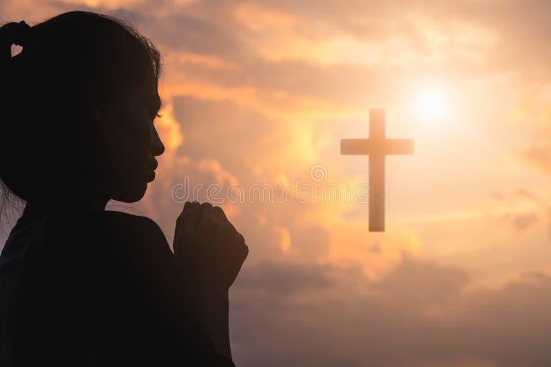 Silhouette de jeune femme priant avec une croix au lever de soleil, fond de concept de Christian Religion image libre de droits