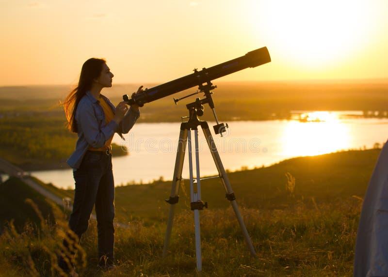Silhouette de jeune femme regardant la vue par le télescope le coucher du soleil d'été photos stock