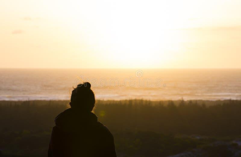 Silhouette de jeune femme regardant le coucher du soleil sur la Côte Pacifique de l'Orégon photo stock