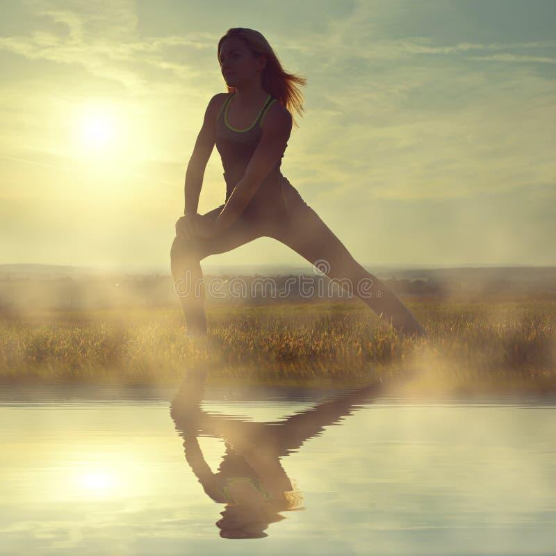 Silhouette de jeune femme s'étendant sur un pré photo libre de droits