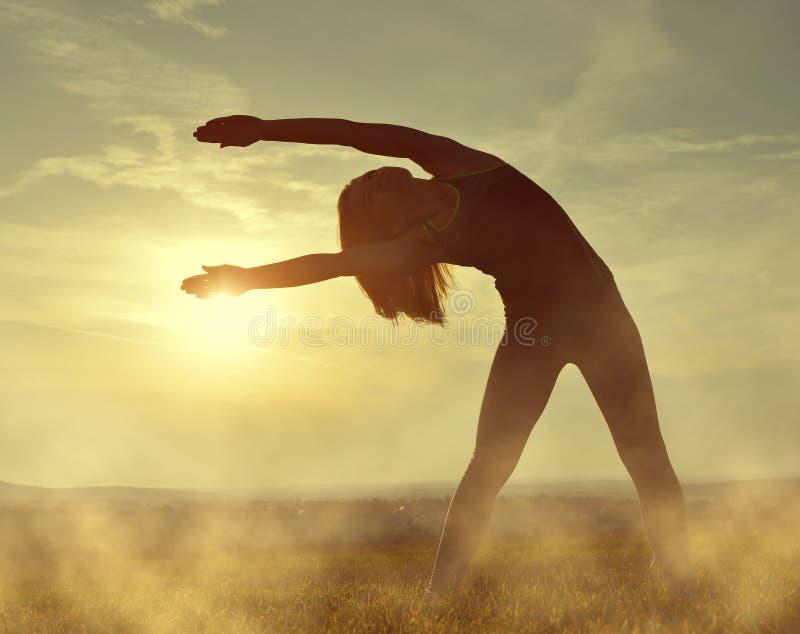 Silhouette de jeune femme s'étendant sur un pré photos libres de droits
