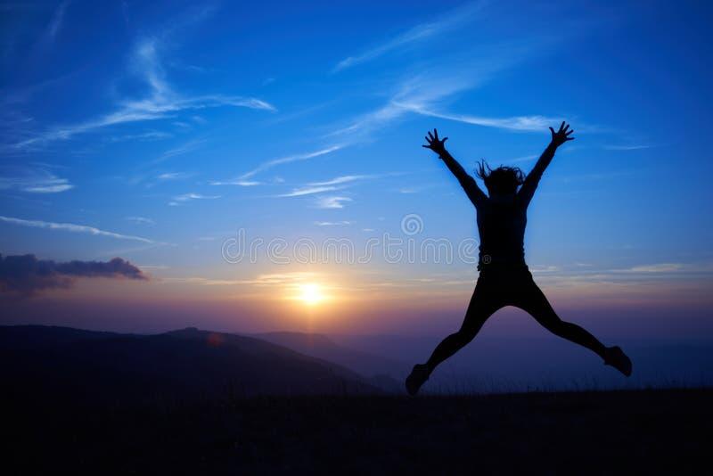 Silhouette de jeune femme sautante photographie stock