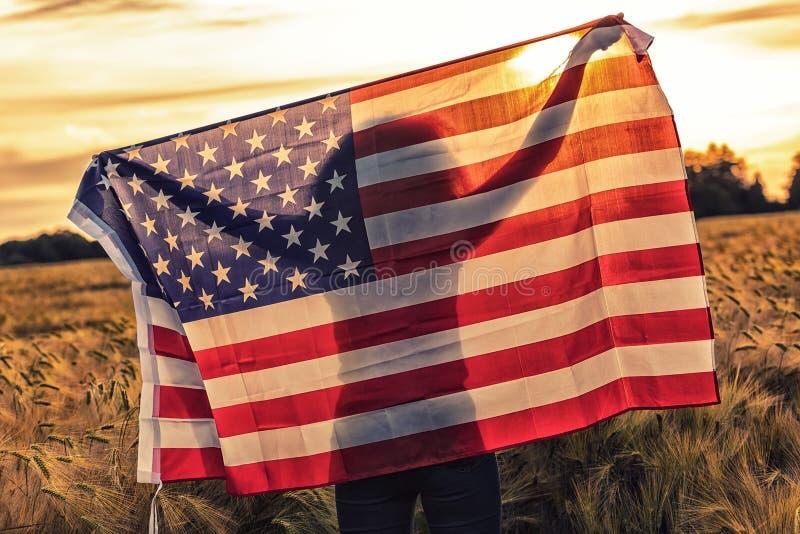 Silhouette de jeune femme tenant le drapeau des Etats-Unis dans le domaine au coucher du soleil images stock
