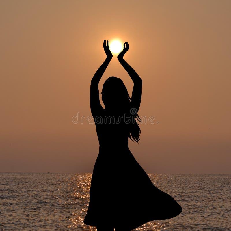 Silhouette de jeune femme tenant le soleil dans des ses mains image stock