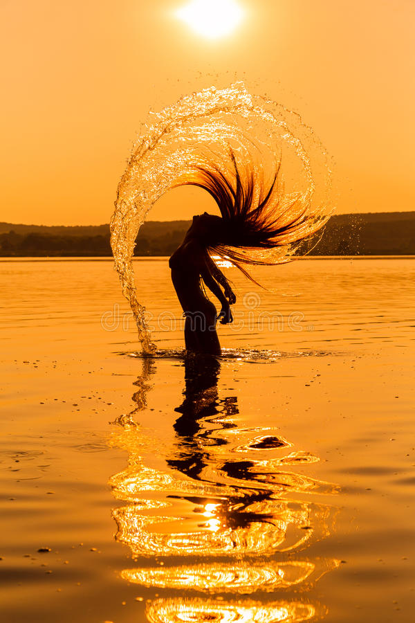 Silhouette de jeune fille dans l'eau éclaboussant leurs cheveux image libre de droits