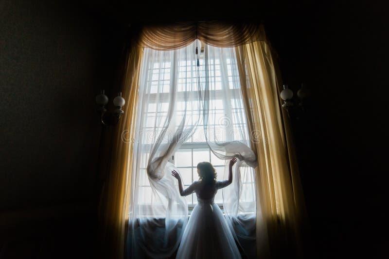 Silhouette de jeune mariée heureuse dans des rideaux en ouverture blancs de robe images stock