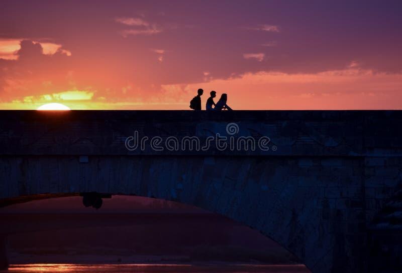 Silhouette de jeunes amis sur un coucher du soleil coloré en renvoyant la maison, croisant un pont photo stock