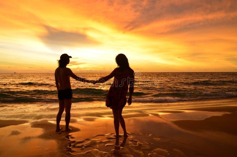 Silhouette de jeunes couples dans l'amour sur la plage quand coucher du soleil photographie stock libre de droits
