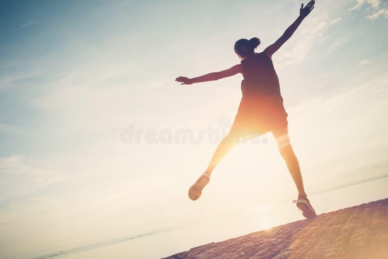 Silhouette de jolie femme sautant près de l'océan Dépenses du bons temps et amusement images stock