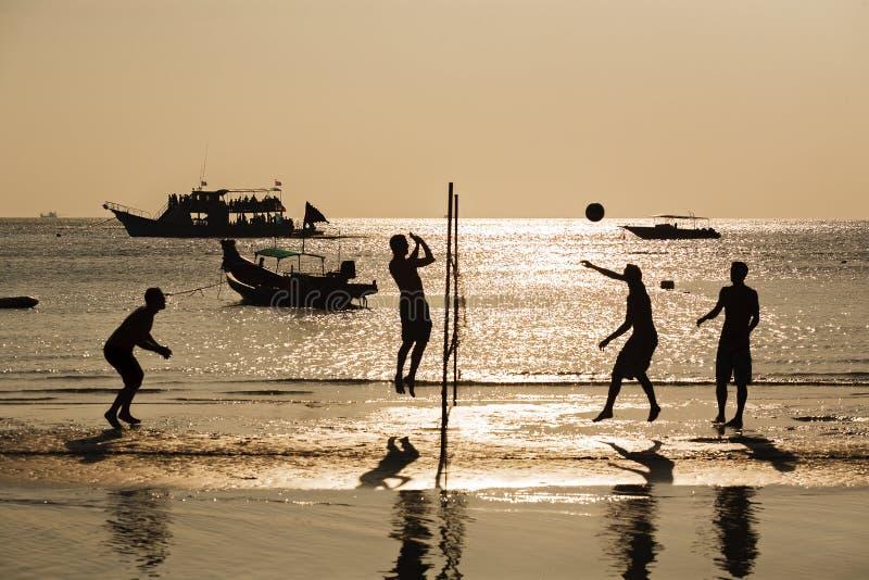 Silhouette de joueur de volleyball de plage dans le coucher du soleil image stock