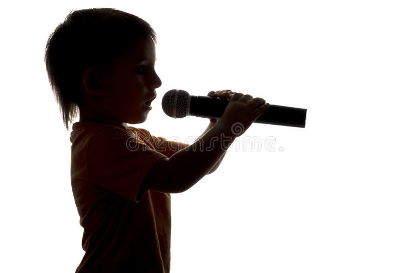 Silhouette de karaoke de chant de petit enfant dans le microphone images stock