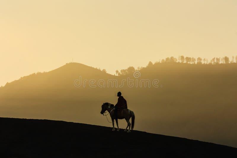 Silhouette de l'équitation au bâti Bromo dans Java-Orientale, Indonesi photographie stock libre de droits