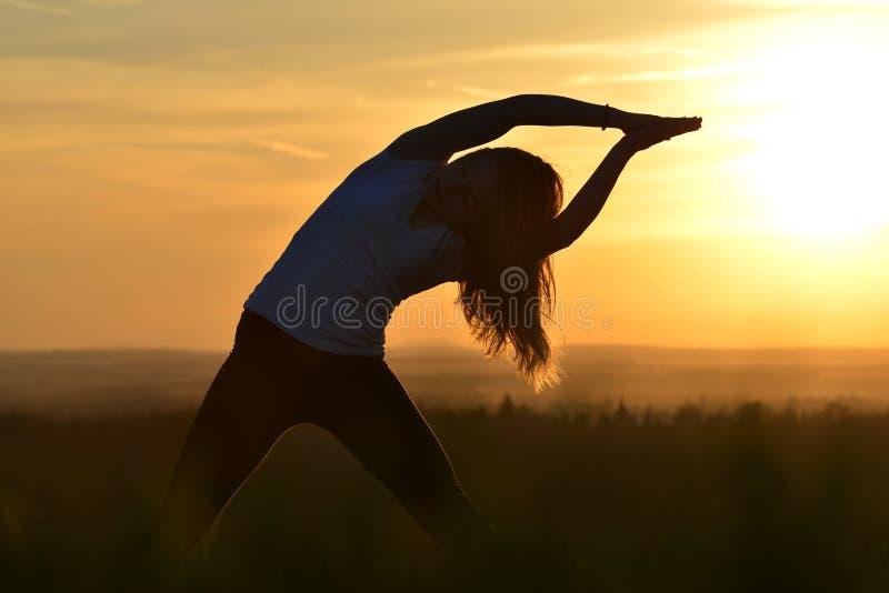 Silhouette de l'étirage de jeune femme photos stock