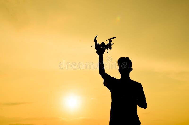 Silhouette de l'agriculteur employant le bourdon ? t?l?commande images libres de droits