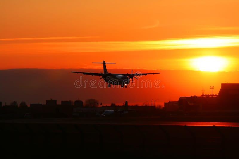 Silhouette de l'avion d'atterrissage sur un coucher du soleil. image stock