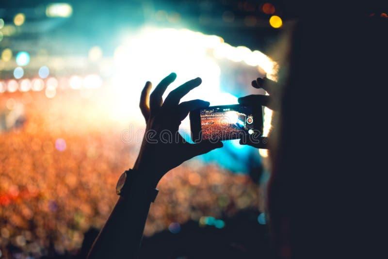 Silhouette de l'homme à l'aide du smartphone pour prendre une vidéo à un concert Mode de vie moderne avec le hippie prenant des p photos stock