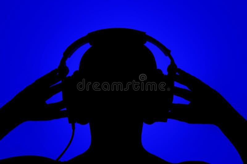 Silhouette de l'homme avec des écouteurs sur le fond bleu photographie stock libre de droits