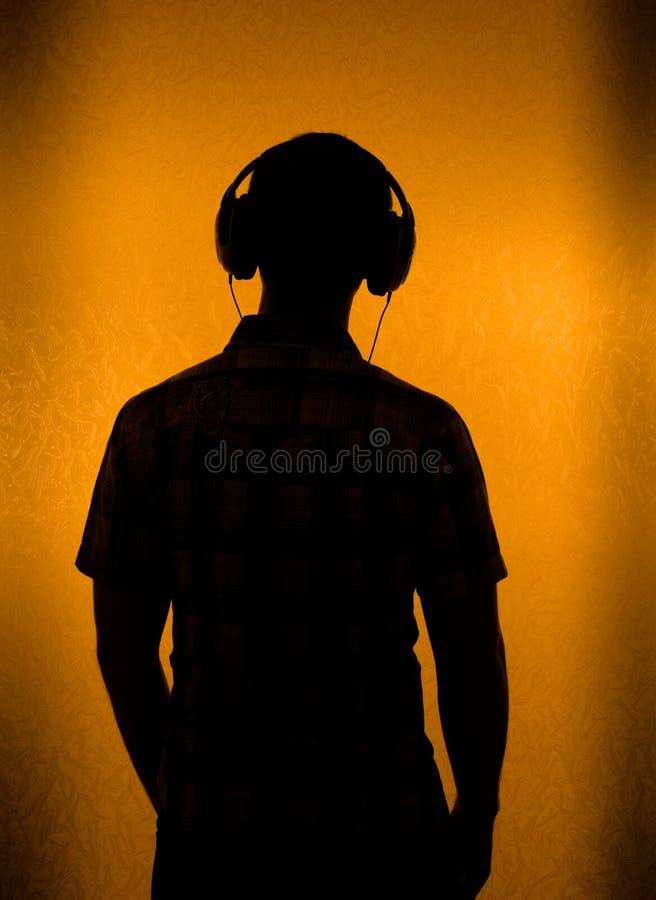 Silhouette de l'homme avec l'écouteur images stock