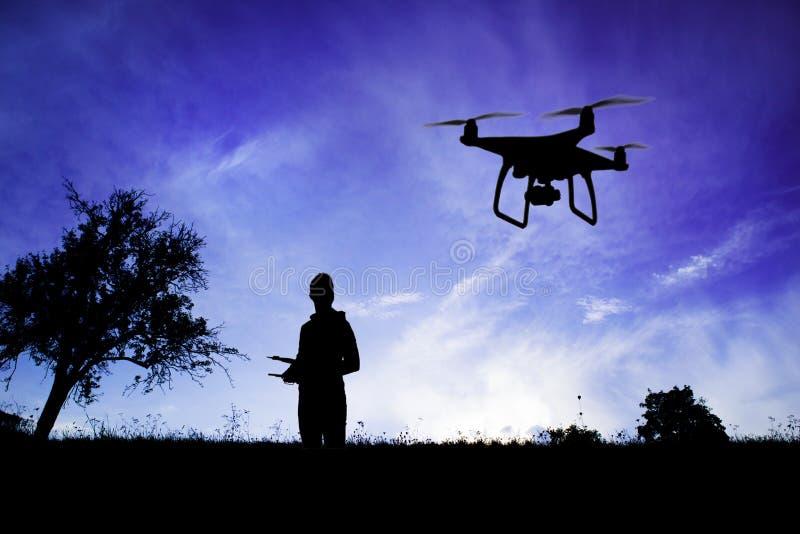 Silhouette de l'homme avec le bourdon de vol en nature au crépuscule photo stock