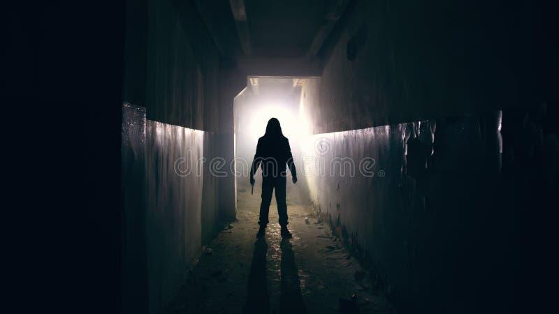 Silhouette de l'homme dans le couloir rampant et fantasmagorique sombre photo stock