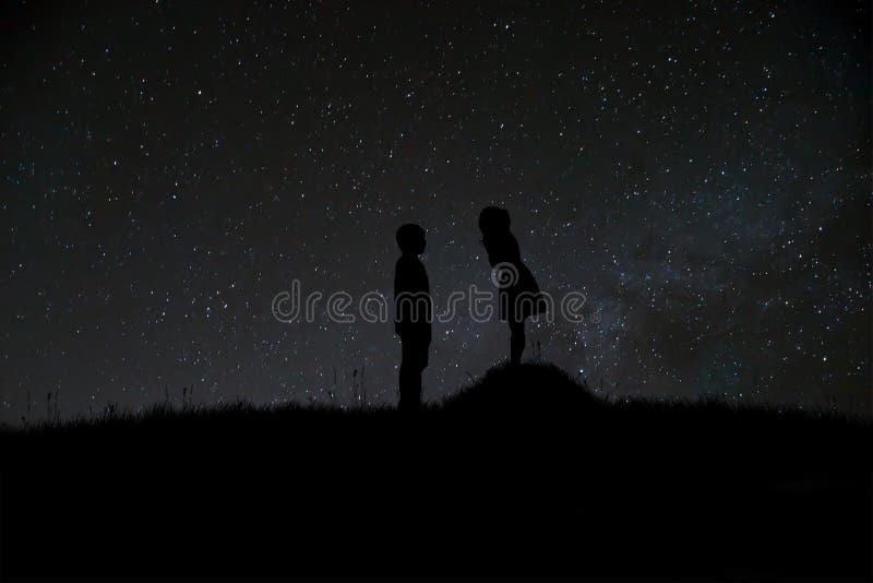 Silhouette de l'homme et de femme au-dessus d'herbe et de colline avec des milieux de manière laiteuse d'étoile, valentine romant image stock