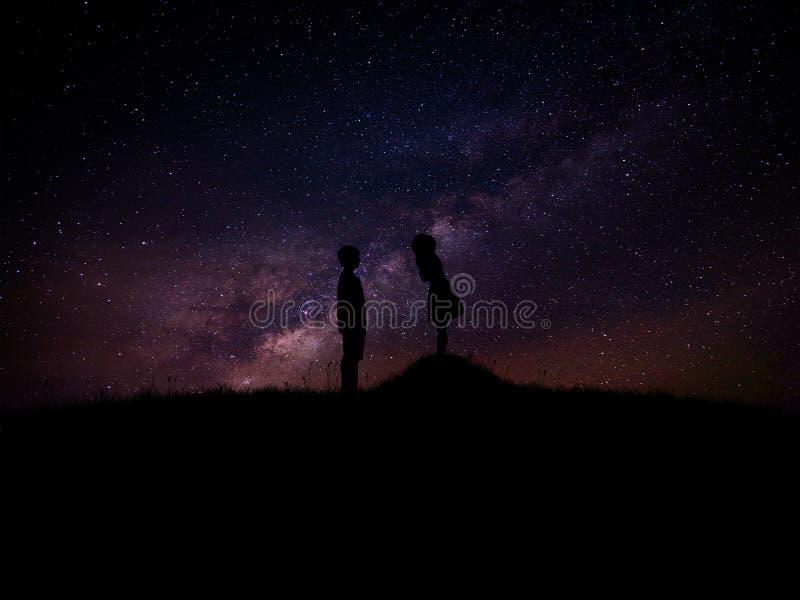 Silhouette de l'homme et de femme au-dessus d'herbe et de colline avec des milieux de manière laiteuse d'étoile, valentine romant images libres de droits