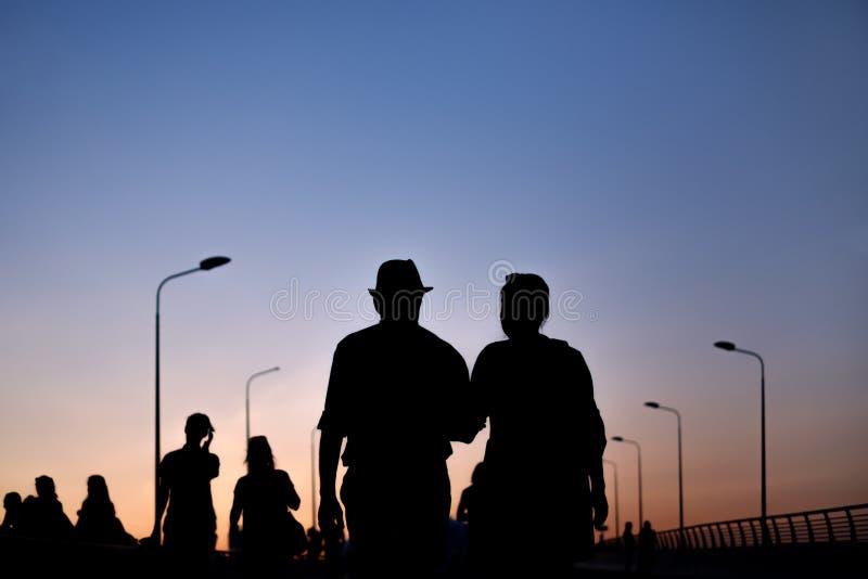 Silhouette de l'homme et de la femme de couples marchant sur le coucher du soleil photo stock