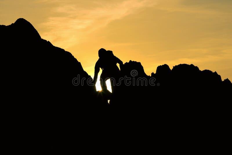 Silhouette de l'homme s'élevant sur la montagne de roche au coucher du soleil photographie stock libre de droits