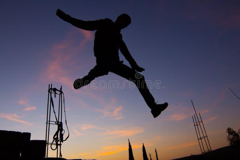 Silhouette de l'homme sautant sur le fond de coucher du soleil image libre de droits