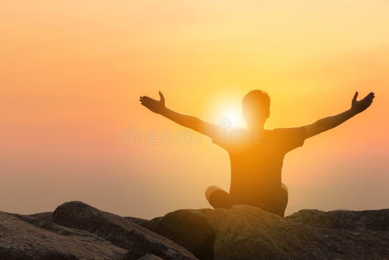 Silhouette de l'homme se reposant avec les mains ouvertes sur une pierre regardant image libre de droits