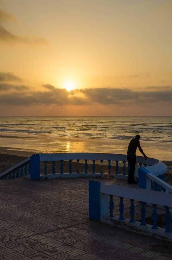 Silhouette de l'homme se tenant à la promenade de plage avec le passage couvert en pierre pendant le coucher du soleil chez Sidi  photos libres de droits