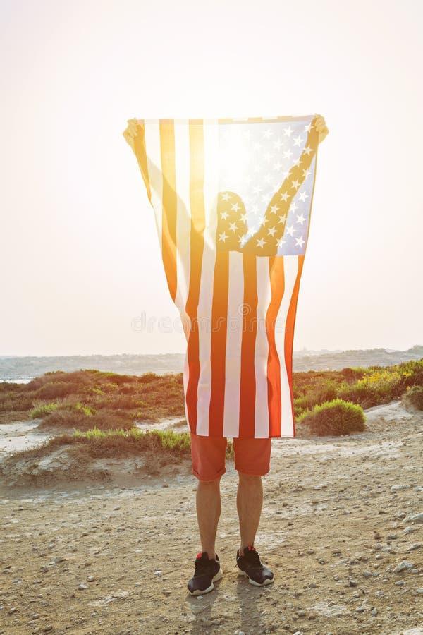 Silhouette de l'homme se tenant dans le drapeau américain augmenté de mains photo stock
