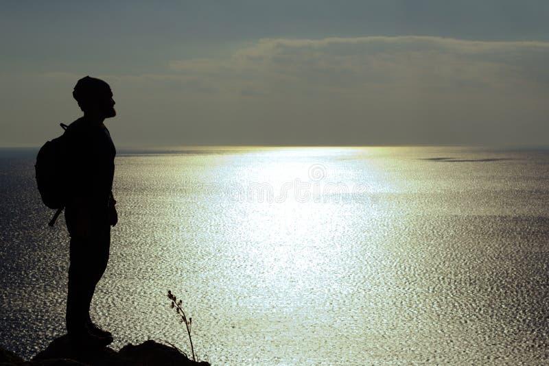 Silhouette de l'homme se tenant sur une roche et regardant la mer images libres de droits