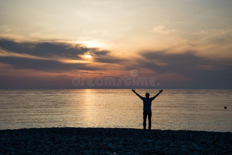 Silhouette de l'homme soulevant ses mains ou bras ouverts quand le soleil se levant  photos libres de droits