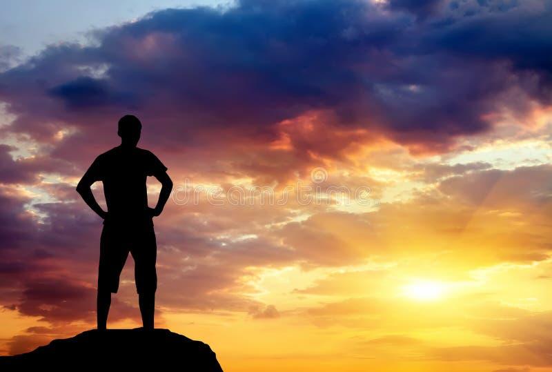 Silhouette de l'homme sur la roche au coucher du soleil. photo libre de droits
