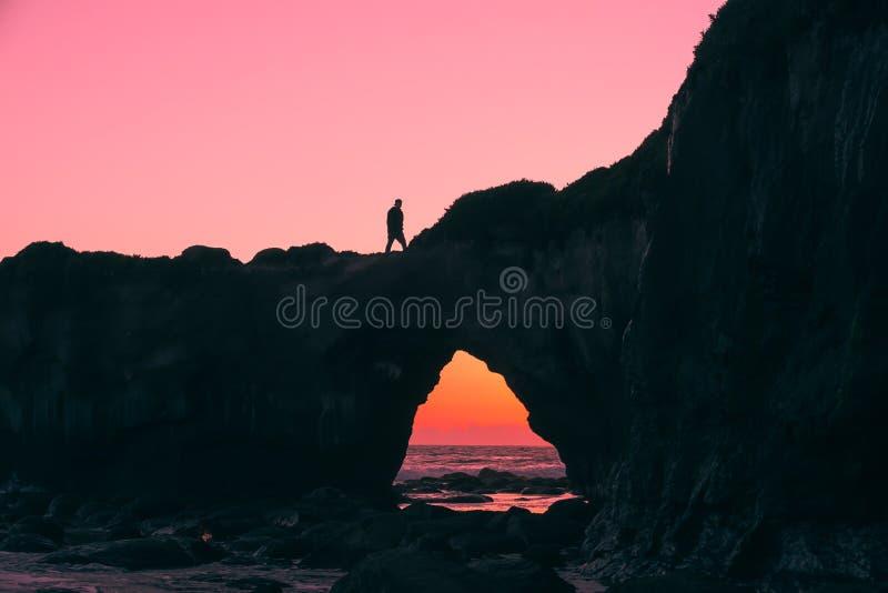 Silhouette de l'homme sur la roche marchant pendant le Nightime photographie stock libre de droits