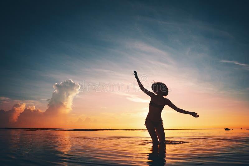 Silhouette de la danse de femme dans l'océan au coucher du soleil photos libres de droits