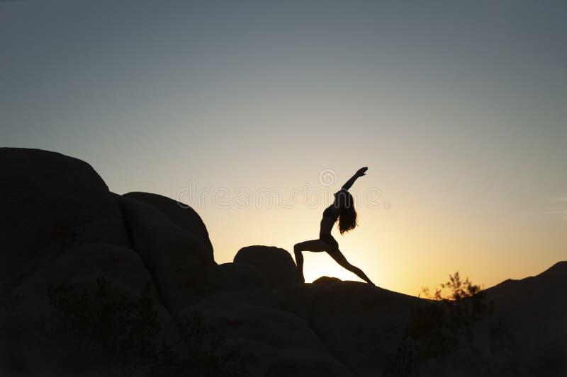 Silhouette de la femme de pose du guerrier du Yoga du désert images stock