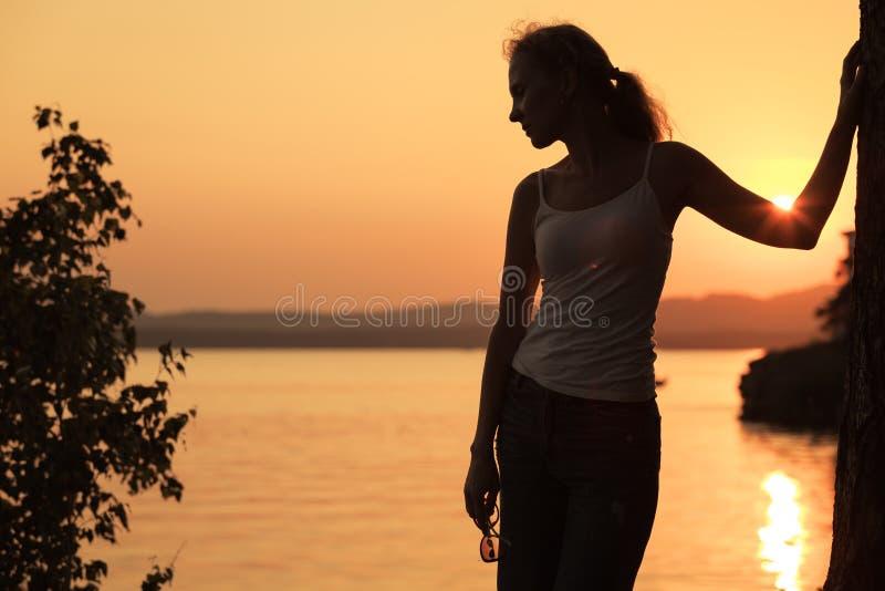 Silhouette de la femme qui se tenant sur la côte du lac photo stock