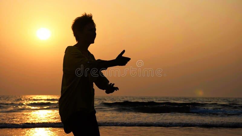 Silhouette de la femme supérieure active pratiquant le chi de tai gymnastique sur la plage sablonneuse images libres de droits
