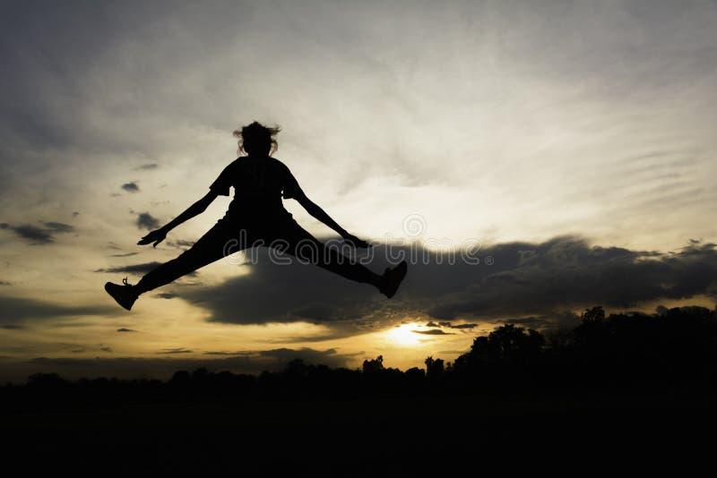 Silhouette de la fille positive et pleine gaie d'énergie sautant dans le ciel pour le concept d'énergie de la vie images libres de droits