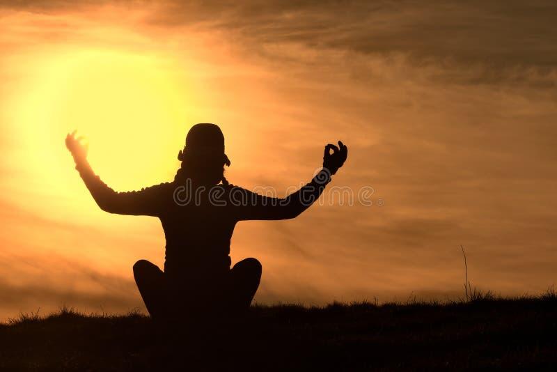 Silhouette de la fille qui pratiquent le yoga photo stock